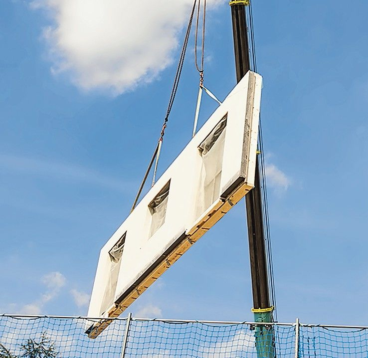 Assembling_a_prefabricated_house_-_wall_is_hanging_on_a_crane