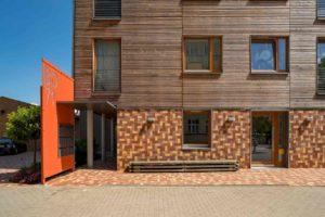 Mehrgenerationenhaus mit Holzfassade und Pflasterklinker-Fassade im Erdgeschoss