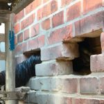 Vor dem Einbringen der Hohlraumdämmung werden am Mauerfuß Öffnungen geschaffen