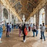 VERSAILLES,_FRANCE_-_May_07,_2016_:_Many_tourist_visiting_Hall_of_Mirrors_in_Versailles_palace_in_France._Versailles_palace_is_the_palace's_most_celebrated_room._Setting_for_many_of_the_ceremonies.