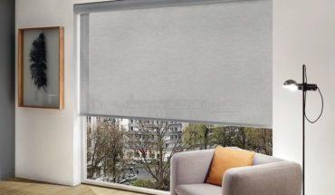 Elegantes_Hotelzimmer_mit_Rollo_in_grau_und_Blick_in_die_Stadt,_Sessel_und_Bilderrahmen